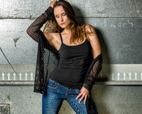 Trendy Woman in blue jeans posing in the grungy underground Stock Photos