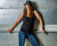 Trendy Woman in blue jeans posing in the grungy underground Stock Photography