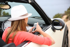 Trendy woman in cabriolet using smartphone Royalty Free Stock Images
