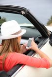 Trendy woman in cabriolet using smartphone Royalty Free Stock Photography