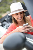 Trendy woman in car using smartphone Royalty Free Stock Photography