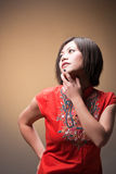 Trendy woman in deep thought. (brown background royalty free stock photo