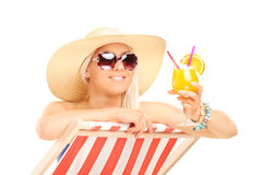 Trendy woman drinking a cocktail on a sun lounger Stock Photo