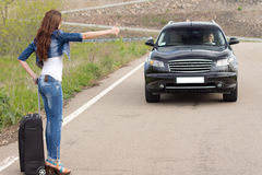 Trendy woman hitchhiking on a country road stock photography