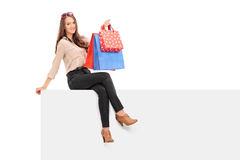 Trendy woman holding shopping bags seated on panel Stock Photos