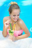 Trendy woman with lemonade in the pool Stock Photography