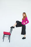 Trendy woman model with chair in pink on isolated background Stock Photo