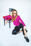 Trendy woman model with chair in pink on isolated background Royalty Free Stock Photos