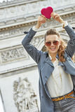 Trendy woman near Arc de Triomphe showing red heart Royalty Free Stock Photography