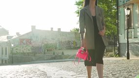 Trendy woman with pink bag walking in slow motion at the street in the morning. Elegance stylish woman with pink bag in hand, black dress and grey coat is stock footage