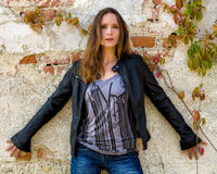 Trendy woman posing in front of a weathered wall. Blue jeans and black leather jacket Stock Photo