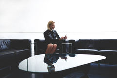 Trendy woman reading text message from her boyfriend on mobile phone during work break in office interior, Stock Photos