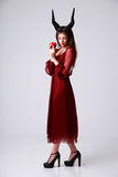 Trendy woman in red dress with apple Stock Images