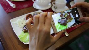 Trendy woman in a restaurant make photo of food with mobile phone camera for social network stock footage