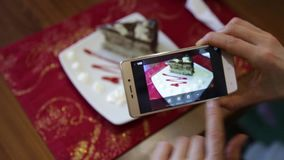 Trendy woman in a restaurant make photo of food with mobile phone camera for social network stock video
