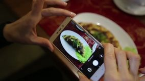 Trendy woman in a restaurant make photo of food with mobile phone camera for social network stock video footage