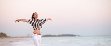Trendy woman on seacoast in evening rejoicing. Trendy woman in white pants and striped shirt on the seacoast in the evening rejoicing royalty free stock image