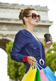 Trendy woman with shopping bags and cup of coffee in Paris. Get your bags ready for the Paris shopping. young trendy woman in sunglasses with cup of coffee in Stock Image