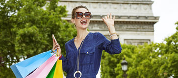 Trendy woman with shopping bags handwaving in Paris, France Royalty Free Stock Photography