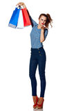 Trendy woman with shopping bags on white blowing air kiss. Shopping. The French way. Full length portrait of smiling trendy woman with shopping bags of the Royalty Free Stock Photography