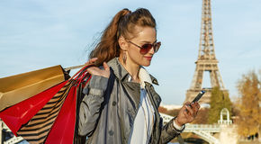Trendy woman with shopping bags writing sms near Eiffel tower Royalty Free Stock Photography