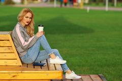 Trendy woman in sitting on the bench in city park. Drinking takeaway coffee and writing or drawing something in notebook Stock Photography