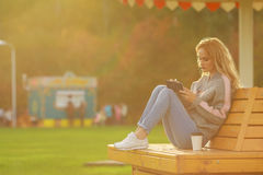 Trendy woman in sitting on the bench in city park. Drinking takeaway coffee and writing or drawing something in notebook Stock Image