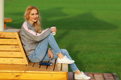 Trendy woman in sitting on the bench in city park. Drinking takeaway coffee and writing or drawing something in notebook Royalty Free Stock Photo
