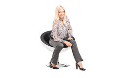 Trendy woman sitting on a modern chair Stock Image