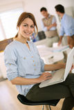 Trendy woman sitting on stool to use a laptop Royalty Free Stock Image