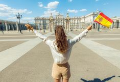 Trendy woman with Spain flag rejoicing against Royal Palace. Seen from behind trendy woman with Spain flag rejoicing against Royal Palace royalty free stock image