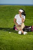 Trendy woman speaking on phone on golf course. Stylish young brunette in elegant sportswear sitting on green course with golf equipment and talking on smartphone royalty free stock photo