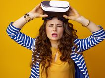 Trendy woman  on yellow with VR glasses has tired eyes Royalty Free Stock Image