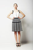 Trendy Woman in Stripped Skirt and T-Shirt standing. Urban Clothing Collection Royalty Free Stock Photos
