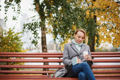 Trendy woman in stylish coat sitting Stock Photo