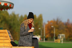 Trendy woman in stylish coat sitting on the bench in city park. Urban scene outdoors. Royalty Free Stock Image