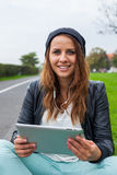 Trendy woman with Tablet PC wearing headphones outdoors. Royalty Free Stock Images