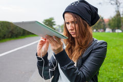 Trendy woman with Tablet PC wearing headphones outdoors. Stock Photos