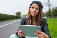 Trendy woman with Tablet PC wearing headphones outdoors. Stock Photo