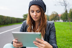 Trendy woman with Tablet PC wearing headphones outdoors. Royalty Free Stock Image