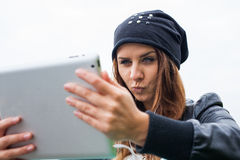 Trendy woman with Tablet PC wearing headphones outdoors. Stock Photography
