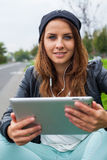 Trendy woman with Tablet PC wearing headphones outdoors. Stock Image