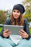 Trendy woman with Tablet PC wearing headphones outdoors. Royalty Free Stock Photo