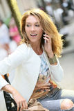 Trendy woman talking on phone. Trendy girl talking on phone in the street Royalty Free Stock Photo