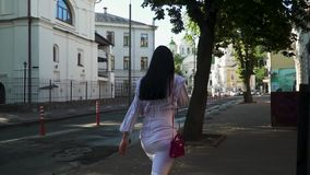 Trendy woman is walking at the street in the morning and talking on phone. Elegant woman in sunglasses, white skirt and stripped blouse is walking at urban stock video