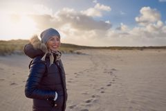Trendy woman in a warm autumn outfit standing on a beach at sunset. Casting a long shadow across the sand looking to the side with a happy smile stock photography