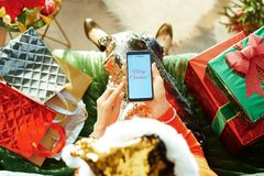 Trendy woman writing Merry Christmas email on smartphone
