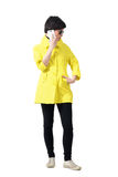 Trendy woman in yellow raincoat talking on the phone looking down Royalty Free Stock Image