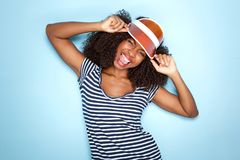 Trendy young african woman in cap sticking out tongue over blue background Royalty Free Stock Photo