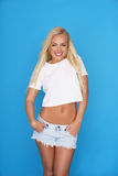 Trendy young blond woman in denim shorts Royalty Free Stock Photography